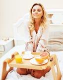 Blond kvinna för ung skönhet som har frukosten i tidig solig mor för säng Royaltyfria Bilder