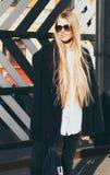 Blond kvinna för ungt långt hår i solglasögon och en trendig dräkt som poserar på den varma våraftonen för gata Mode Arkivfoto