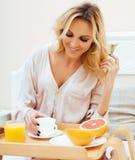 Blond kvinna f?r ung sk?nhet som har frukosten i den tidiga soliga morgonen f?r s?ng, inre rum f?r prinsessahus arkivbilder