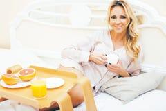 Blond kvinna f?r ung sk?nhet som har frukosten i den tidiga soliga morgonen f?r s?ng, inre rum f?r prinsessahus, sund livsstil fotografering för bildbyråer