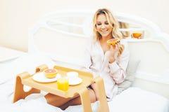 Blond kvinna f?r ung sk?nhet som har frukosten i den tidiga soliga morgonen f?r s?ng, inre rum f?r prinsessahus, sund livsstil arkivbild