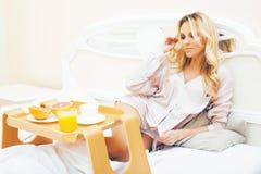 Blond kvinna f?r ung sk?nhet som har frukosten i den tidiga soliga morgonen f?r s?ng, inre rum f?r prinsessahus, sund livsstil royaltyfri foto