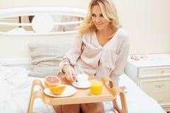 Blond kvinna för ung skönhet som har frukosten i den tidiga soliga morgonen för säng, inre rum för prinsessahus Royaltyfri Bild