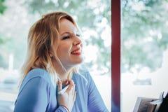 Blond kvinna i blåttklänning i kafé royaltyfri foto