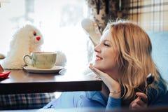 Blond kvinna i blåttklänning i kafé Fotografering för Bildbyråer