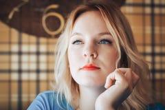 Blond kvinna i blåttklänning i kafé Arkivfoton