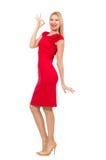Blond kvinna i den scharlakansröda klänningen som isoleras på viten Fotografering för Bildbyråer
