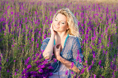 Blond kvinna i det violetta fältet Arkivbild