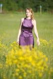 Blond kvinna i en purpurfärgad klänning Royaltyfri Bild