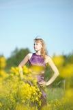 Blond kvinna i en purpurfärgad klänning Fotografering för Bildbyråer