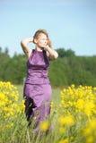 Blond kvinna i en purpurfärgad klänning Royaltyfri Fotografi