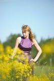 Blond kvinna i en purpurfärgad klänning Arkivfoto
