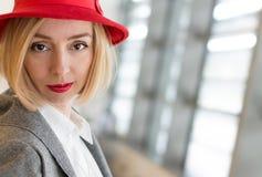 Blond kvinna i en Red Hat Arkivbild