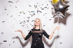 Blond kvinna i hållande stjärnaballong för svart klänning med klipska konfettier på partiet Arkivfoto