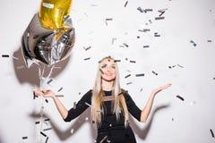 Blond kvinna i hållande stjärnaballong för svart klänning med klipska konfettier på partiet Arkivbild
