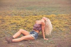Blond kvinna i kortslutningar och kängor i fält Arkivbilder