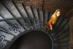 Blond kvinna i lång klänning på trappan Fotografering för Bildbyråer