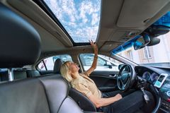 Blond kvinna i modern bil Regndroppar på ett glass tak av bilen royaltyfria foton