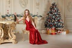 Blond kvinna i röd klänning med exponeringsglas av vitt vin eller champagne som placerar på en stol i lyxig inre jul min version  fotografering för bildbyråer