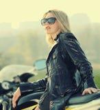 Blond kvinna i solglasögon på en sportmotorcykel arkivfoto