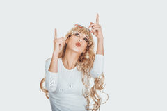 Blond kvinna i solglasögon som pekar upp Fotografering för Bildbyråer