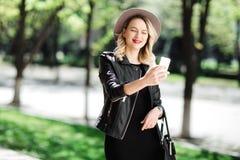 Blond kvinna i svart hatt och läderomslag och påse genom att använda mobiltelefonen Ung kvinna som tar selfie Royaltyfri Fotografi