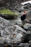 Blond kvinna i svart klänning bland de enorma stenarna på glaciären Mestia Royaltyfria Bilder