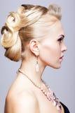 Blond kvinna i svart klänning och halsband fotografering för bildbyråer