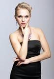 Blond kvinna i svart klänning och halsband royaltyfri foto