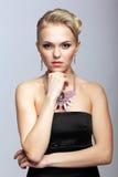 Blond kvinna i svart klänning och halsband Arkivbilder