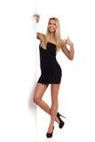 Blond kvinna i svarta Mini Dress Pointing Banner Royaltyfria Bilder