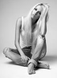 Blond kvinna i trasig jeans och väst Arkivfoto
