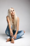 Blond kvinna i trasig jeans och väst Royaltyfri Fotografi