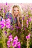 Blond kvinna i violetta blommor Arkivbild