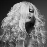 Blond kvinna. Lockigt långt hår. BW modebild Arkivfoton