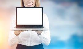 Blond kvinna med bärbara datorn, suddighet Royaltyfri Foto