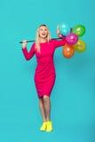 Blond kvinna med ballonger på blått royaltyfri bild