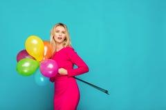 Blond kvinna med ballonger på blått arkivbild