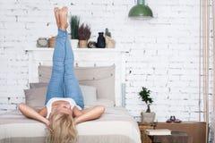 Blond kvinna med ben upp på säng Royaltyfria Bilder