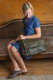 Blond kvinna med den gröna läderkuriren Bag arkivbilder