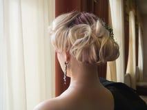 Blond kvinna med den härliga frisyren med hårdetaljtillbehören, bakre sikt för closeup royaltyfri fotografi