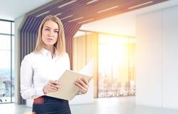 Blond kvinna med en förskriftsbok, futuristiskt kontor Royaltyfri Foto