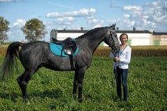 Blond kvinna med en häst Fotografering för Bildbyråer