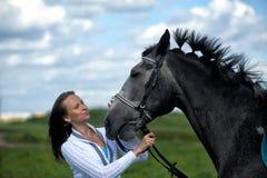 Blond kvinna med en häst Arkivbild