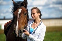 Blond kvinna med en häst Royaltyfria Foton