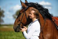 Blond kvinna med en häst Royaltyfria Bilder