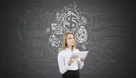Blond kvinna med en minnestavla nära den svart tavlan med dollartecken arkivfoton