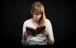 Blond kvinna med exponeringsglas som läser en bok Royaltyfria Foton