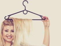 Blond kvinna med hår i klädhängare royaltyfri fotografi