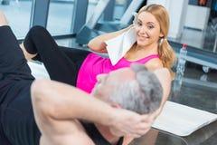 Blond kvinna med handduken som ser den mogna mannen som gör abs Royaltyfria Bilder